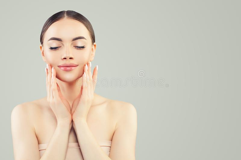 Pretty woman face with clear skin and manicure hands. Skincare, bodycare and facial treatment concept.  royalty free stock photos
