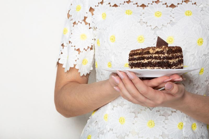 Pretty woman in fashionable dress holding a plate with tasty chocolate cake. Space for text royalty free stock photo