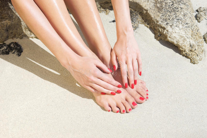 Pretty woman feet with red manicure and pedicure: relaxing on sand. royalty free stock photography