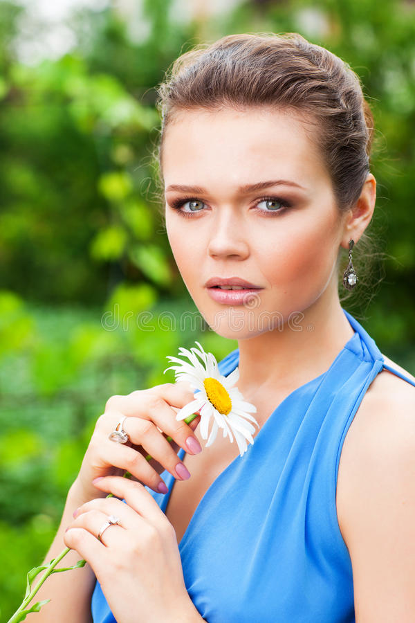Pretty woman with flower in garden stock images