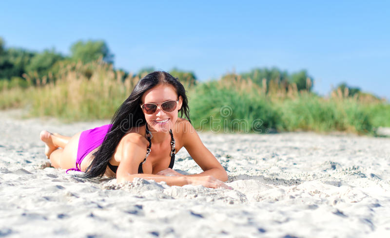 Pretty woman in glasses. Posing on the beach royalty free stock image