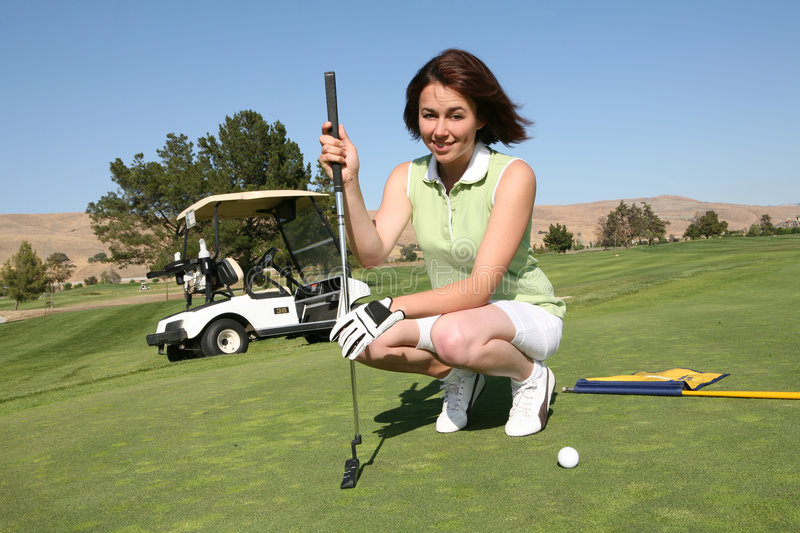 Pretty Woman Golfing. A pretty woman in the middle of a golf game royalty free stock photo