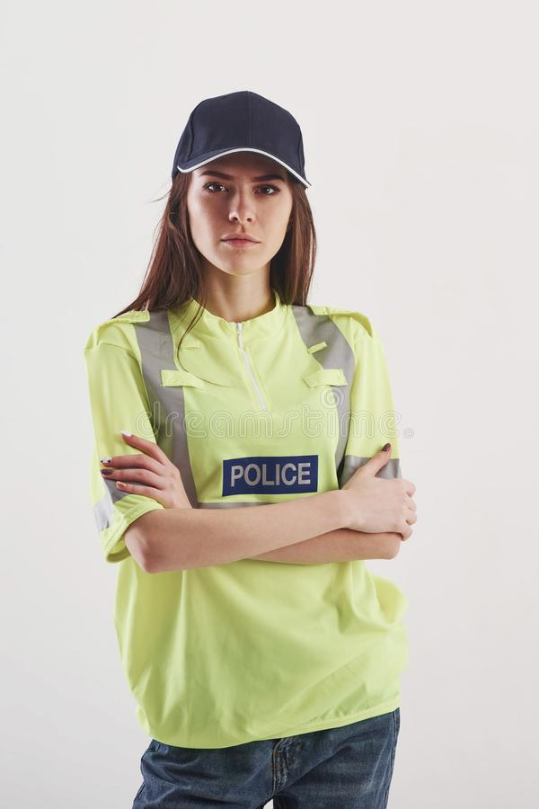 Pretty woman in green police uniform stands against white background in the studio stock images