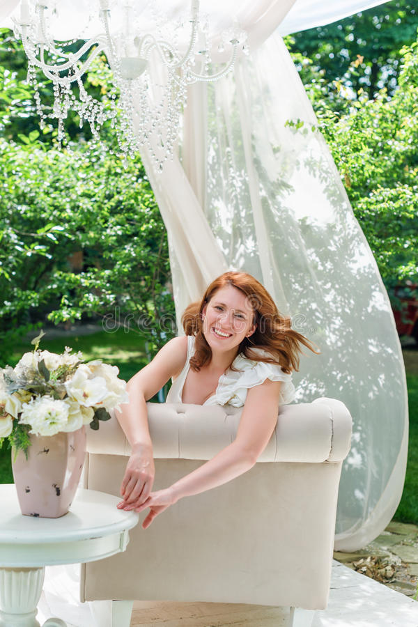 Pretty woman having fun in the summer garden gazebo. Opulent outdoor living area with flowers for celebration, tea party. Pretty woman having fun in the summer stock photos
