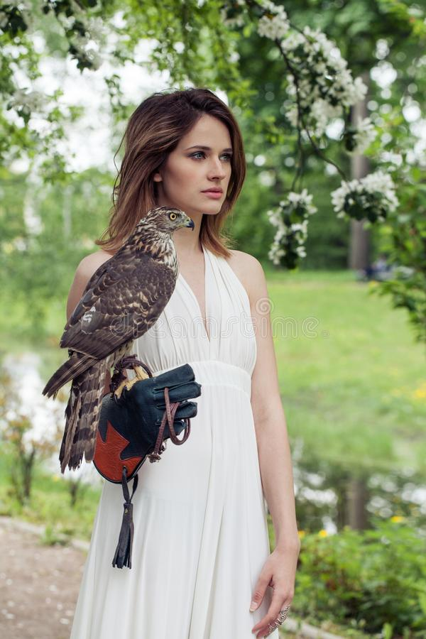 Pretty woman with hawk bird in spring blossom park outdoor stock image