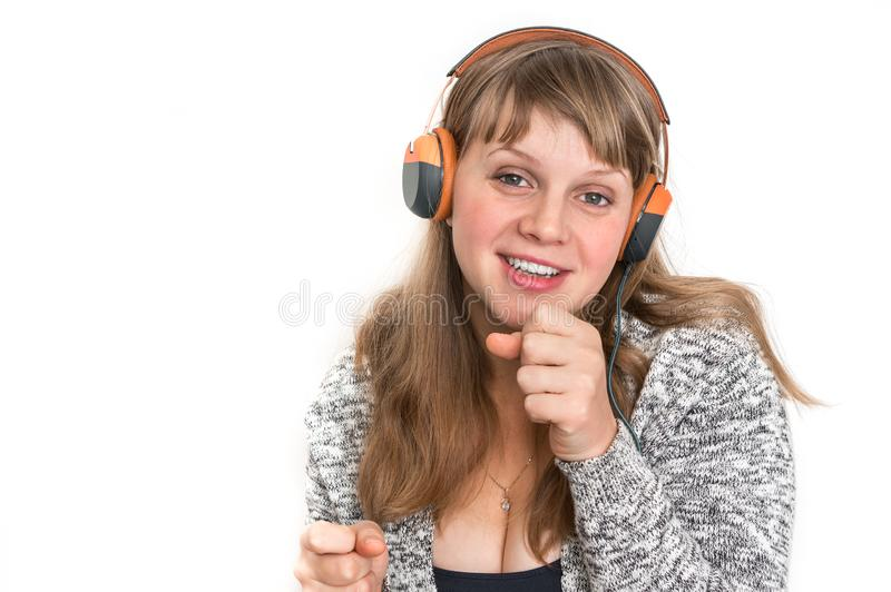 Woman with headphones is listening rock music. Pretty woman with headphones is listening rock music royalty free stock photography