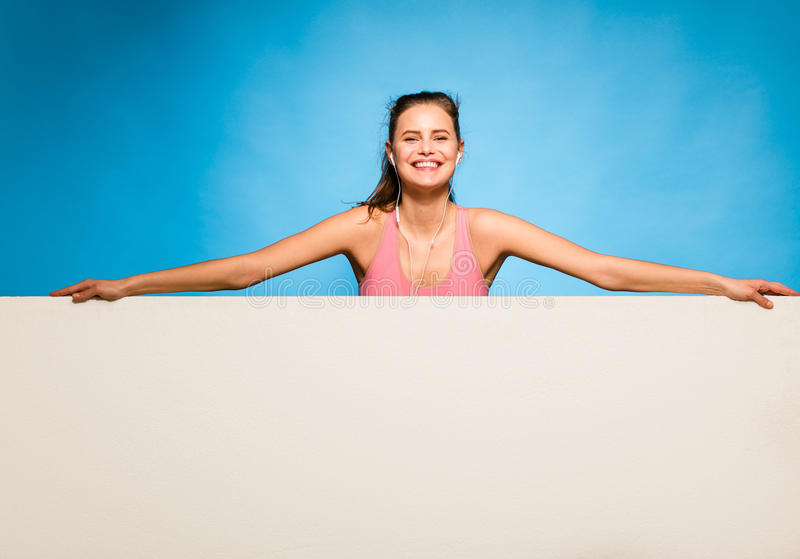 Pretty woman with headsets over an empty panel. Young pretty woman with pink sport shirt and headsets having an empty panel in front on blue background stock photos