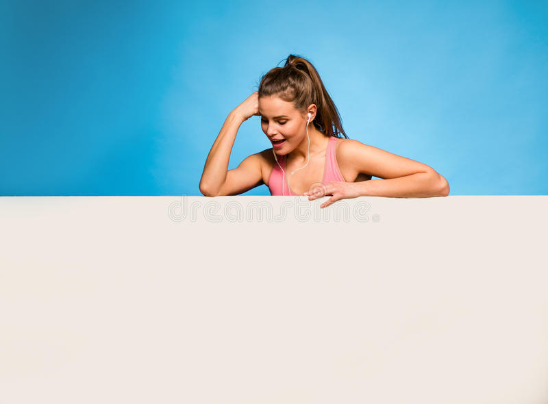 Pretty woman with headsets over an empty panel. Young pretty woman with pink sport shirt and headsets having an empty panel in front on blue background stock images