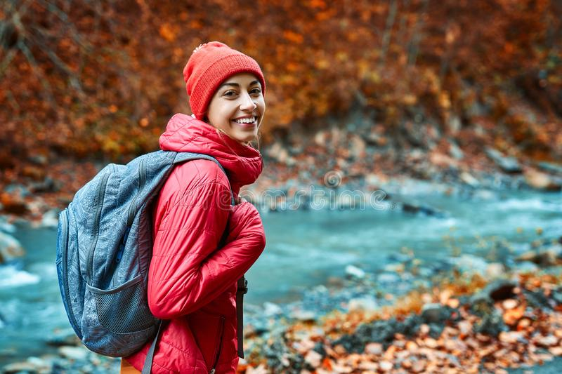 Pretty woman hiker in bright red outdoor clothes is standing outdoors on the mountain river and forest background and stock photos