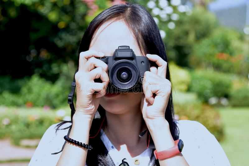 Pretty woman with digital camera. Pretty woman hold a black dslr camera for shooting a picture with blur background of green tree stock photo