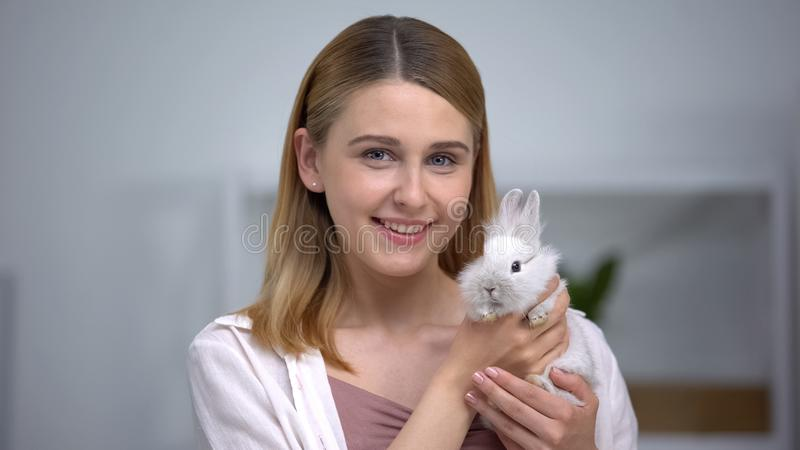 Pretty woman holding bunny and smiling into camera, happy pet owner, adoption. Stock photo royalty free stock photos
