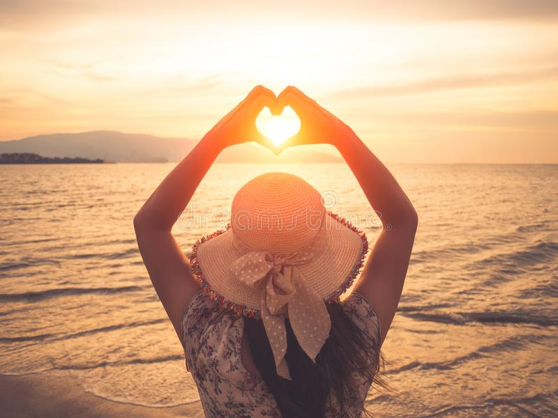 Pretty woman holding hands in heart shape framing setting during sunset on ocean beach royalty free stock photos