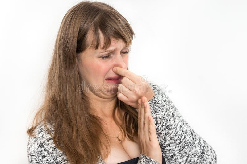 Woman is holding her nose - bad smell concept. Pretty woman is holding her nose - bad smell concept stock photo