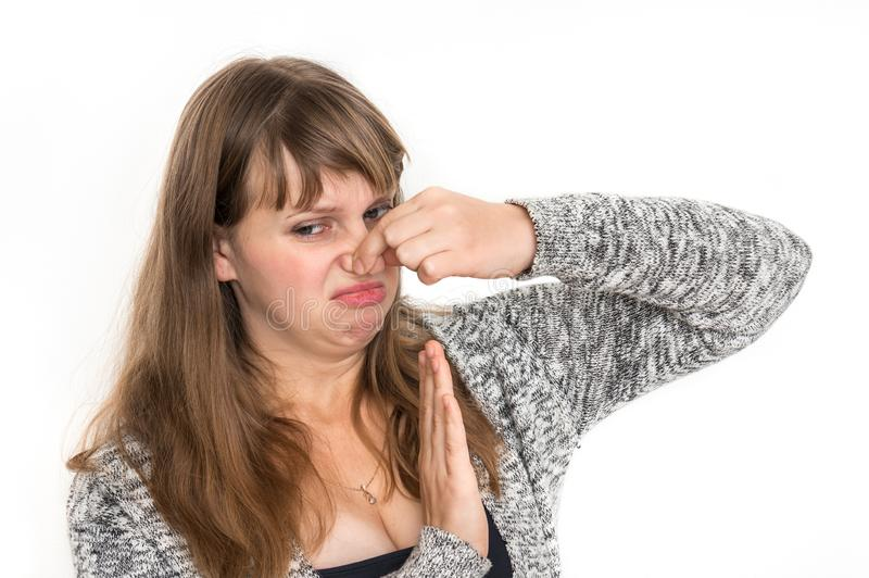 Woman is holding her nose - bad smell concept. Pretty woman is holding her nose - bad smell concept stock image