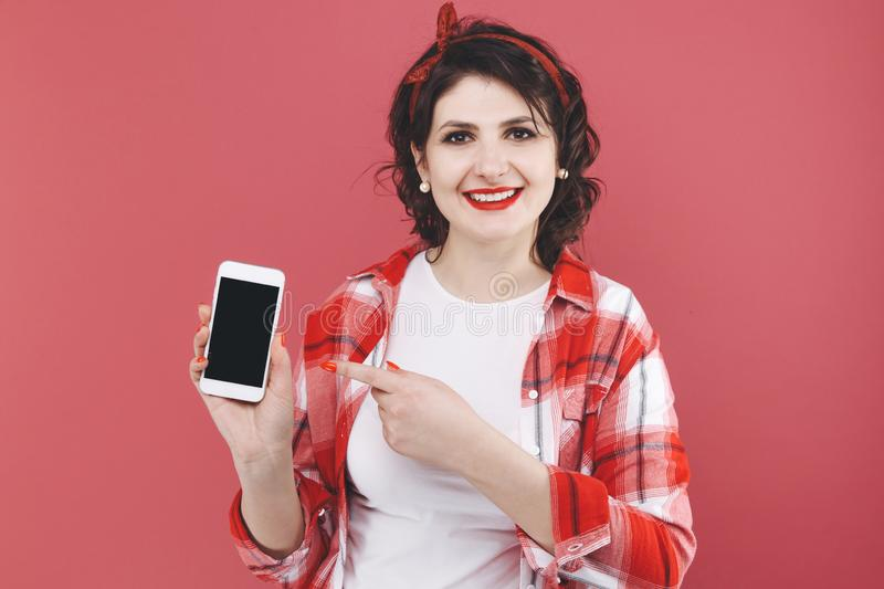 Pretty woman holding phone and smiling in a red studio. royalty free stock photo