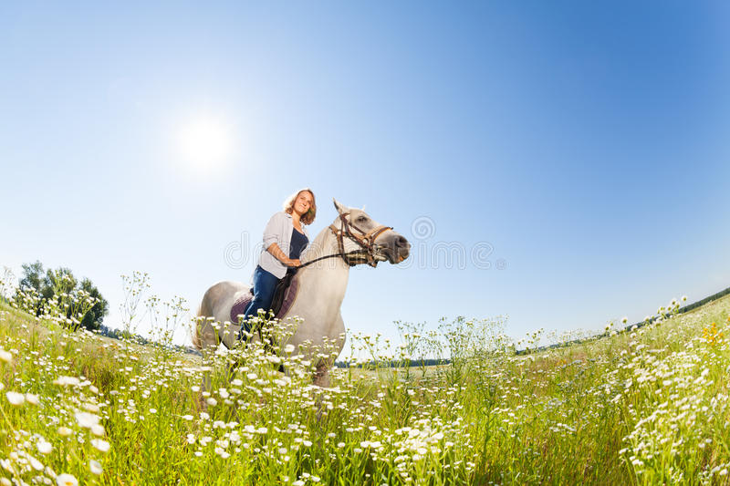 Pretty woman horseriding in the flowery meadow stock photography