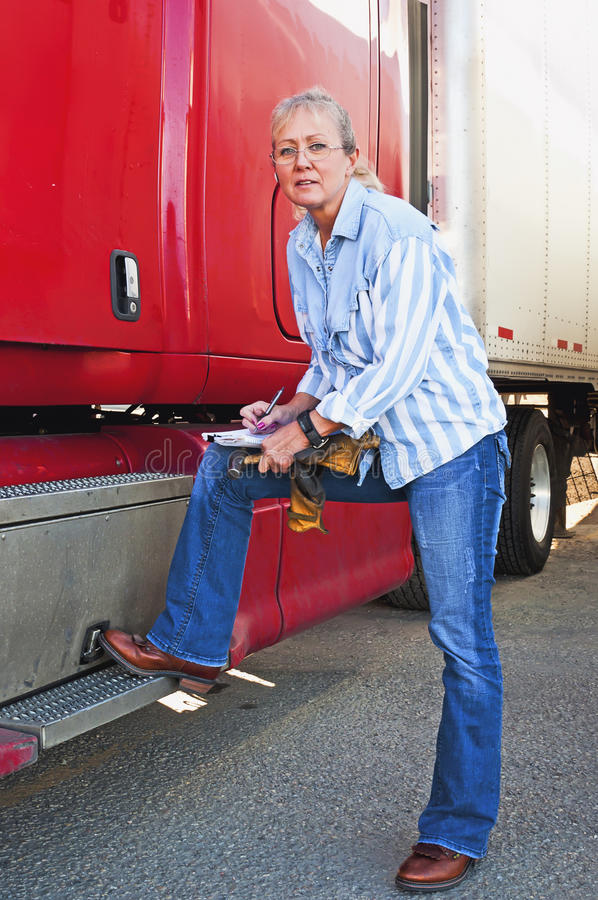 Pretty Woman Inspecting Truck. Pretty adult blonde woman doing a pre-trip inspection on her big truck before starting the delivery run royalty free stock image