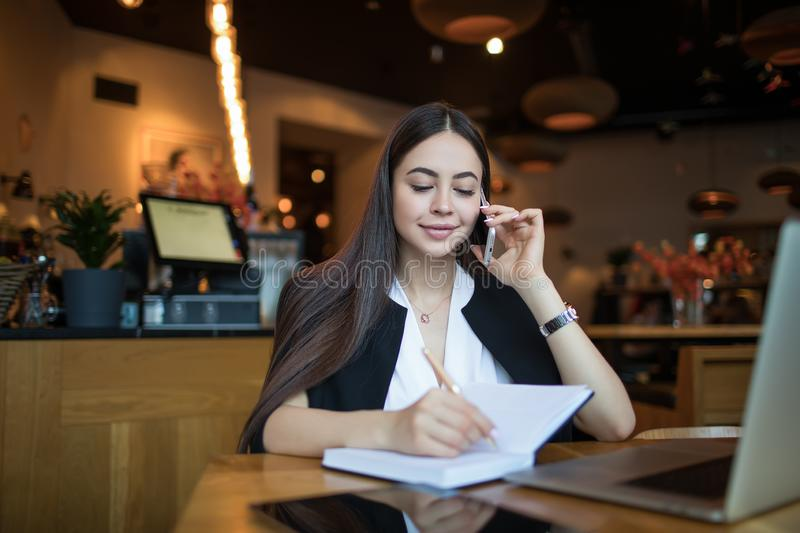 Pretty woman international student writing information in textbook and talking via smartphone stock images