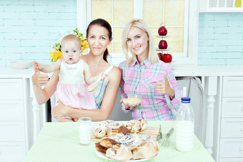 Pretty woman in the kitchen with the baby. royalty free stock photography