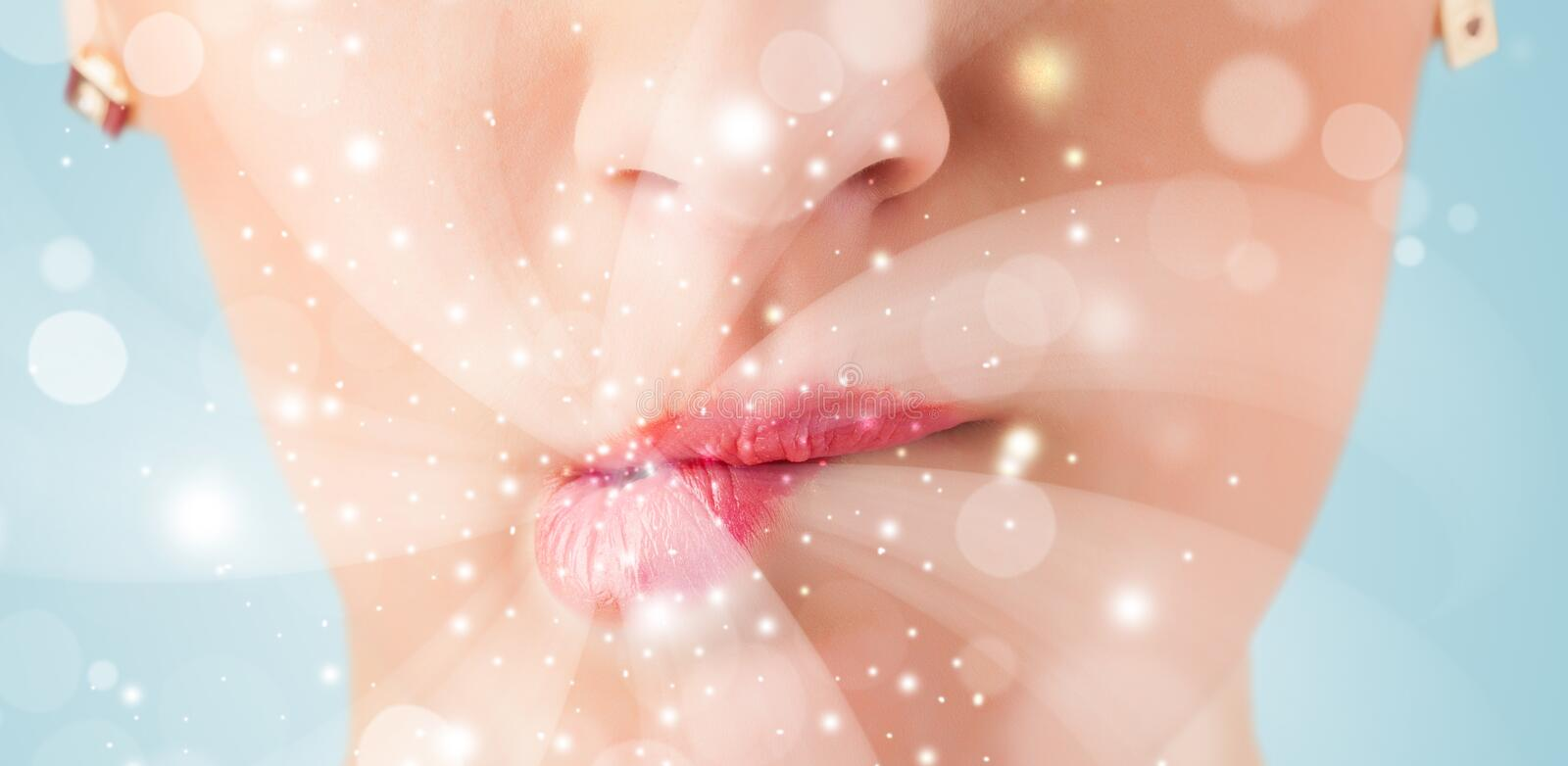 Pretty woman lips blowing abstract white lights. Close up stock image