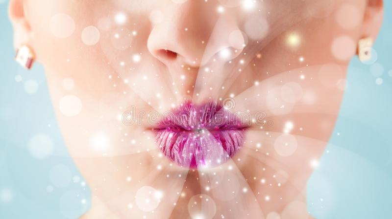 Pretty woman lips blowing abstract white lights. Close up royalty free stock images