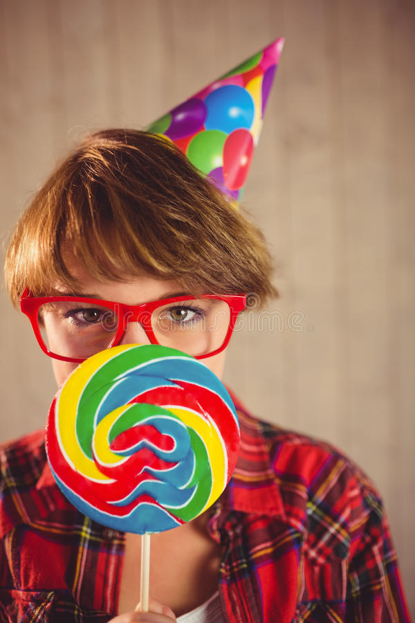 Pretty woman with lollipop and hat party. On wooden planks background royalty free stock photography