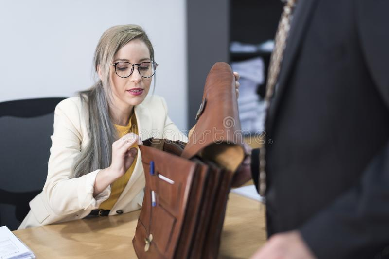 Pretty woman looking in office briefcase royalty free stock image