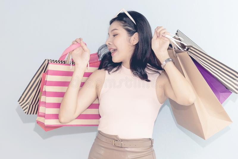 Pretty woman looking at paper bag and happy in shopping. stock photography