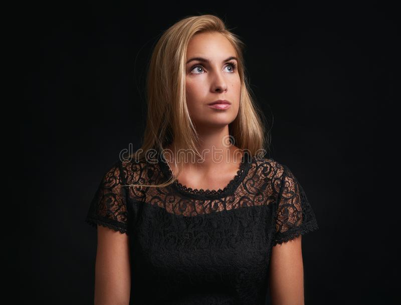 Pretty woman looking up over black background royalty free stock photo