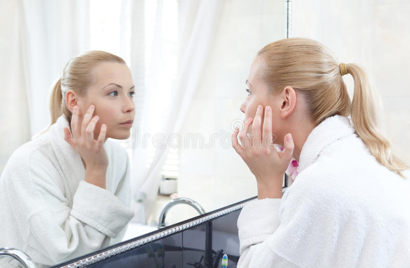Pretty woman looks at her self in mirror stock images