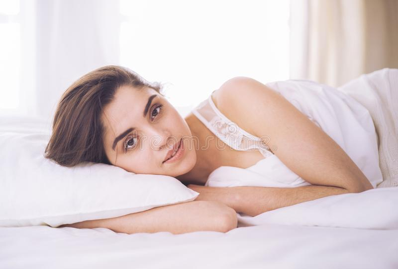 Pretty woman lying down on her bed at home royalty free stock image