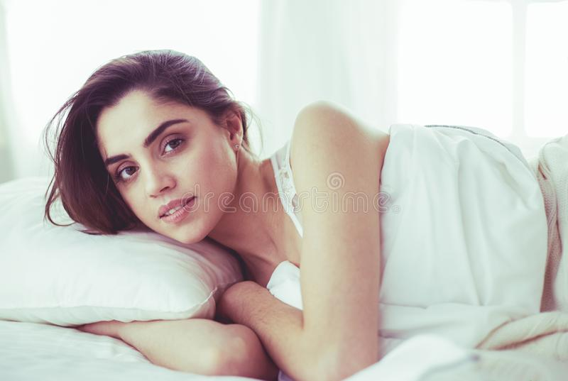 Pretty woman lying down on her bed at home stock image