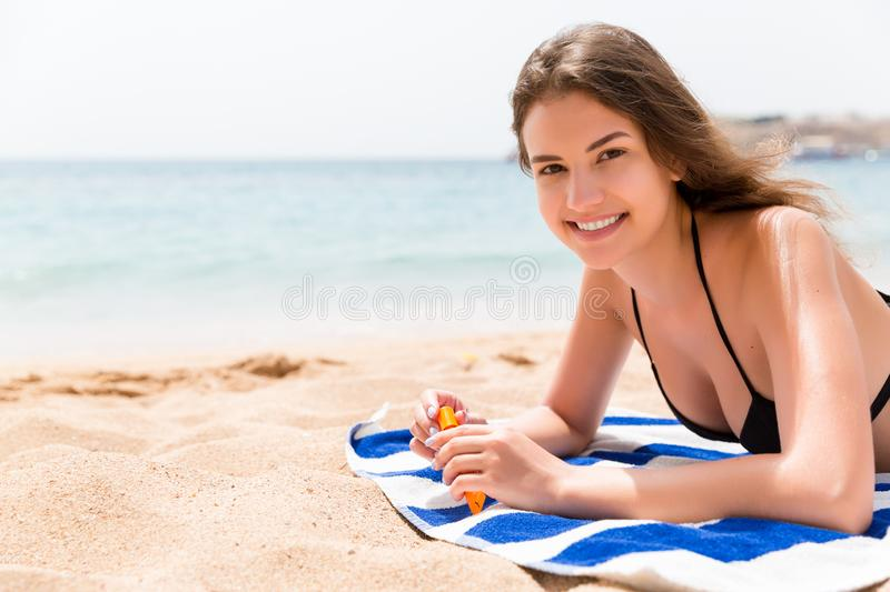Pretty woman is lying on the towel at the beach and opening a tube of sun cream to protect her skin from sunburn stock images
