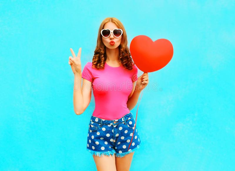 Pretty woman makes an air kiss holds a red balloon in the shape royalty free stock photo