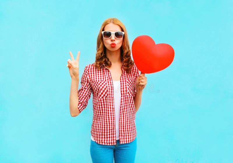 Pretty woman makes an air kiss with red balloon in the shape royalty free stock image