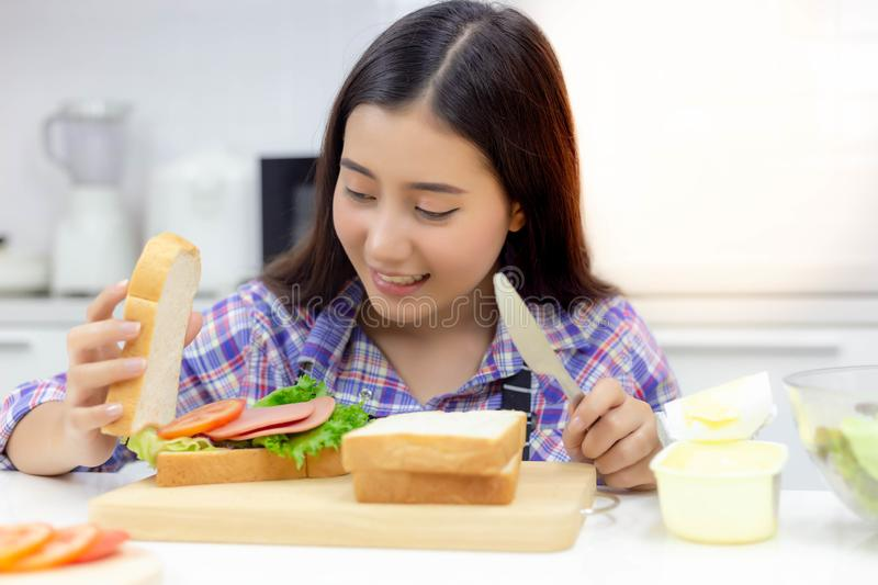Pretty woman is making or cooking sandwich in kitchen for preparing picnic at a park in the morning on weekend holiday. Attractive beautiful woman gets royalty free stock image