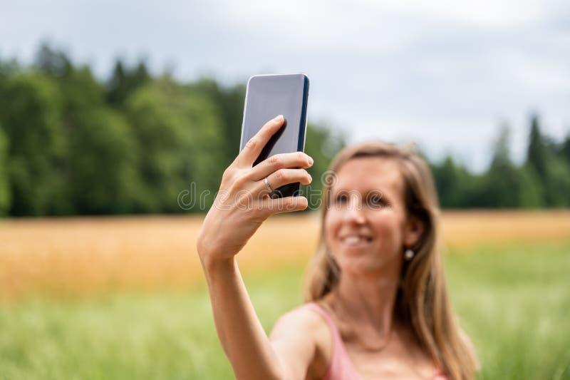 Pretty woman making selfies outside stock photo