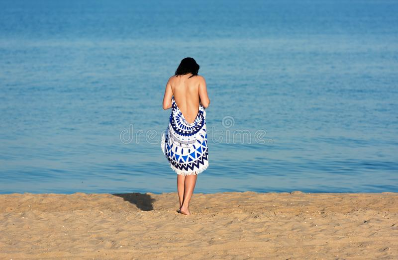 Pretty woman with a mandala round beach tapestry in the seaside. royalty free stock images
