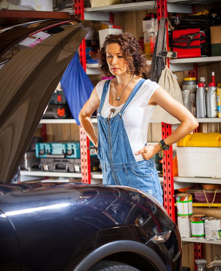 Pretty woman mechanic prepares the car for the travel royalty free stock photos