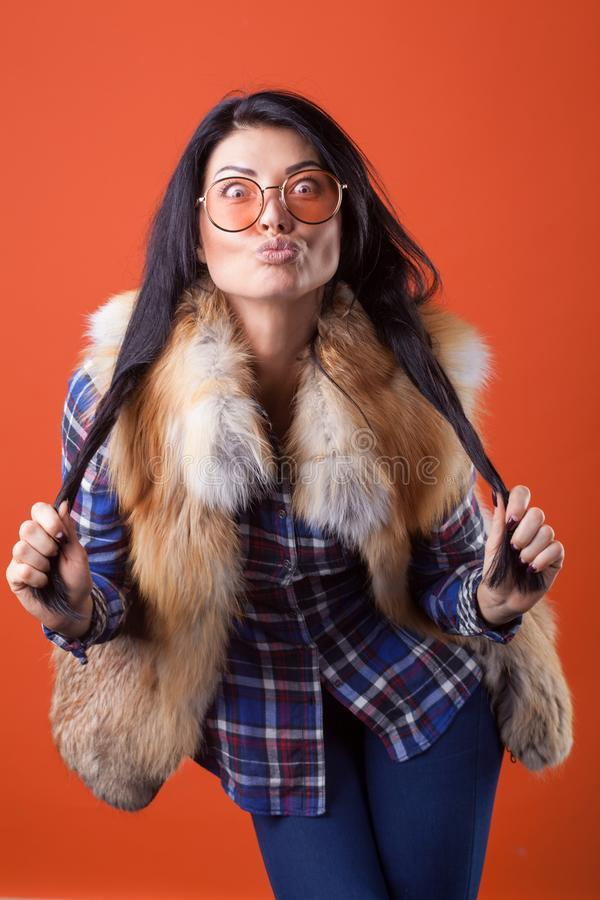 Pretty woman model pose wear plaid shirt and fur vest on the orange studio background stock images