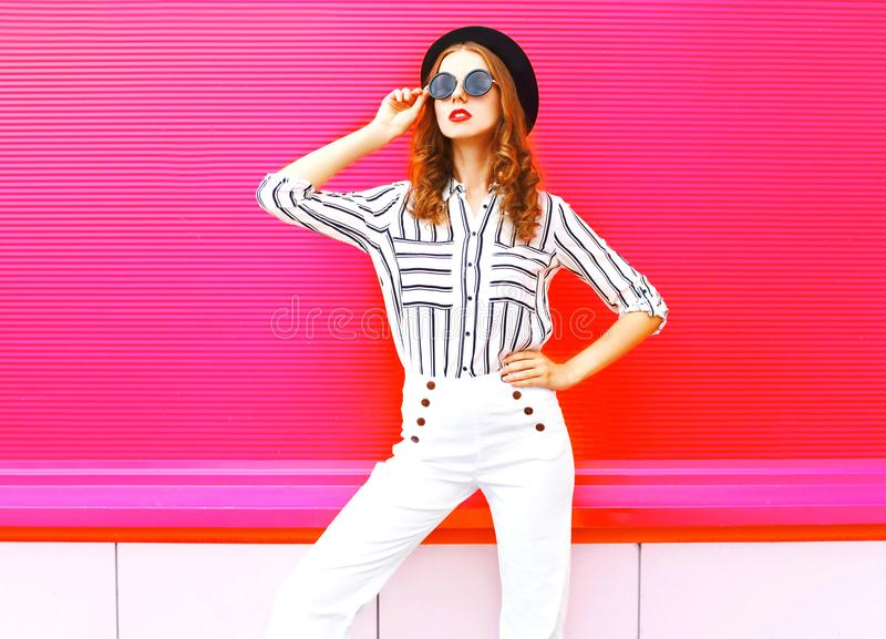 Pretty woman model wearing a black hat sunglasses white pants. Over colorful pink background royalty free stock photo
