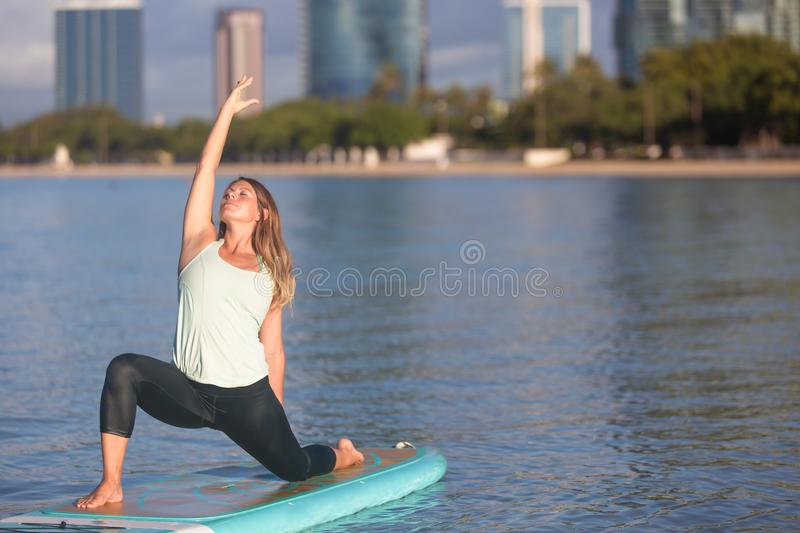 Pretty woman in modified warrior doing SUP Yoga on the water stock photography