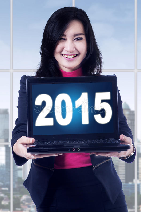 Pretty woman with numbers 2015 on laptop. Attractive businesswoman smiling at the camera while showing numbers 2015 on the laptop royalty free stock photo