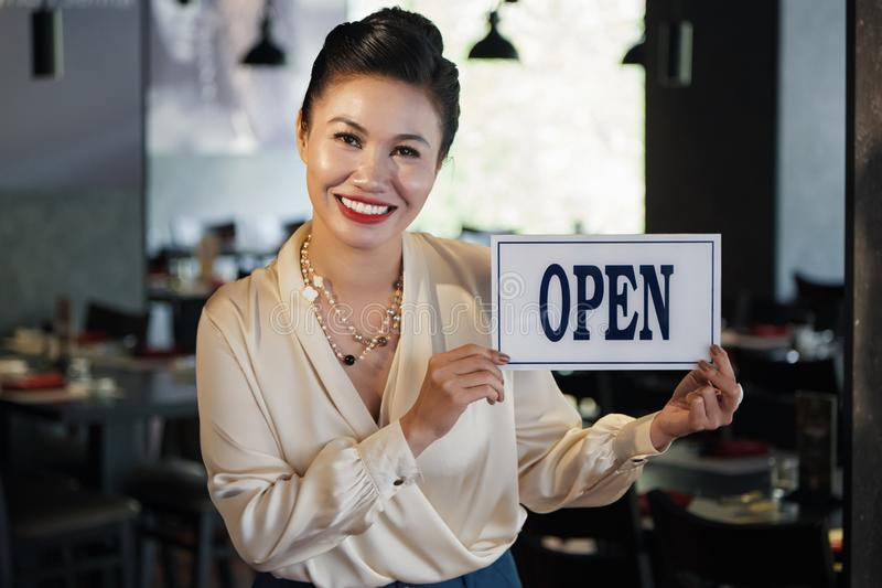 Pretty woman opening her own restaurant. Joyful mature Asian business lady opening her restaurant royalty free stock photo