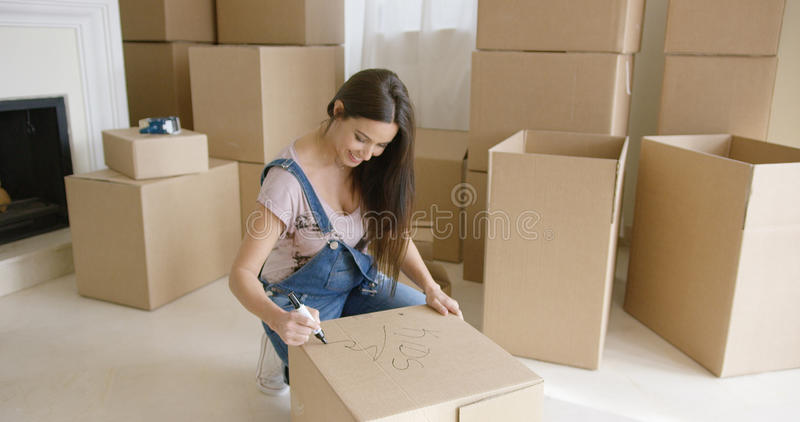 Pretty woman packing up her personal belongings. Attractive woman packing up her personal belongings as she prepares to move house kneeling down writing the stock photo