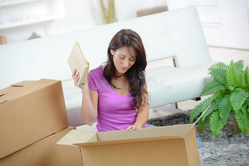Pretty woman packing up personal belongings. Pretty woman packing up her personal belongings stock photo
