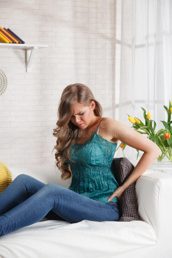 Pretty woman in pain on the sofa. Young woman with painful stomach cramps at home stock photos