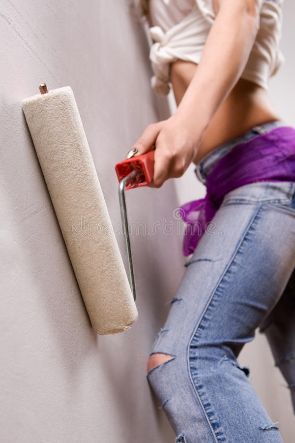 Pretty woman with painting roller stock photography