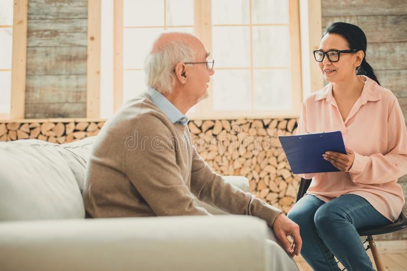 Pretty woman in pink blouse working with pensioner. Calm pensioner sitting. Pretty women in pink blouse working with pensioner in retirement house and discussing royalty free stock image
