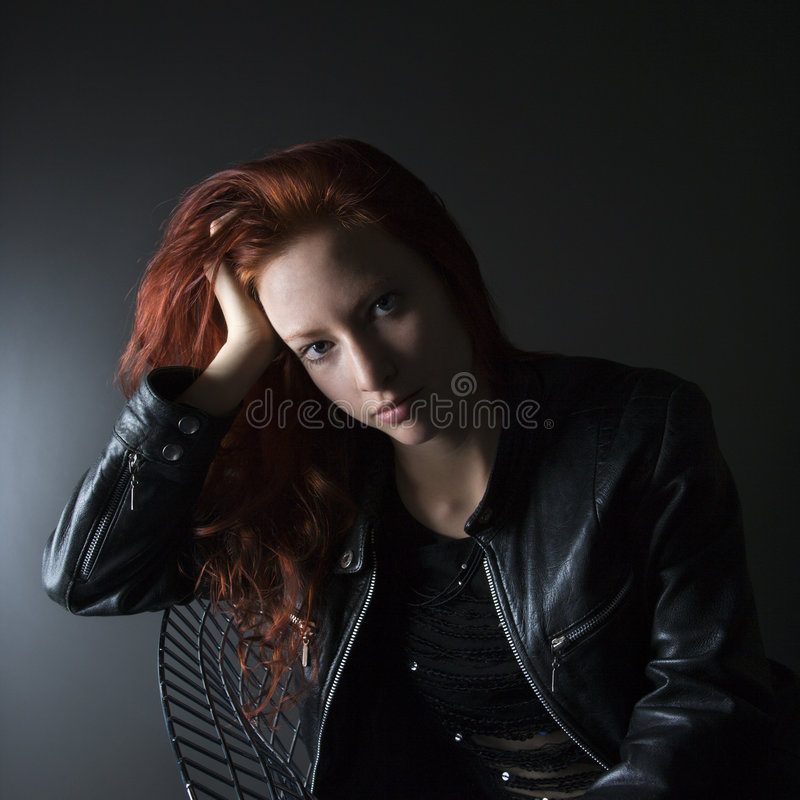 Pretty woman portrait. Portrait of pretty redhead young woman sitting in chair resting head on hand royalty free stock images